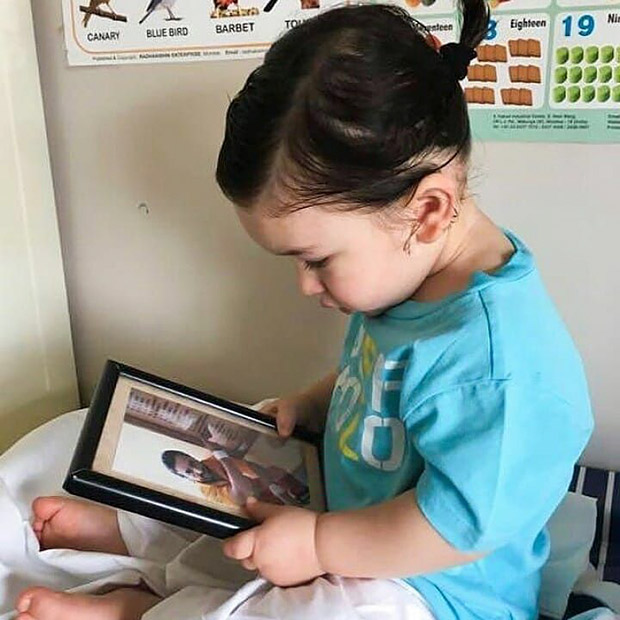 Taimur Ali Khan dons a cute ponytail; stares at daddy Saif Ali Khan's photo