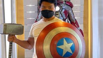 Shang-Chi's Simu Liu strikes a pose with Captain America's Shield & Thor's Mjolnir at Marvel headquarters
